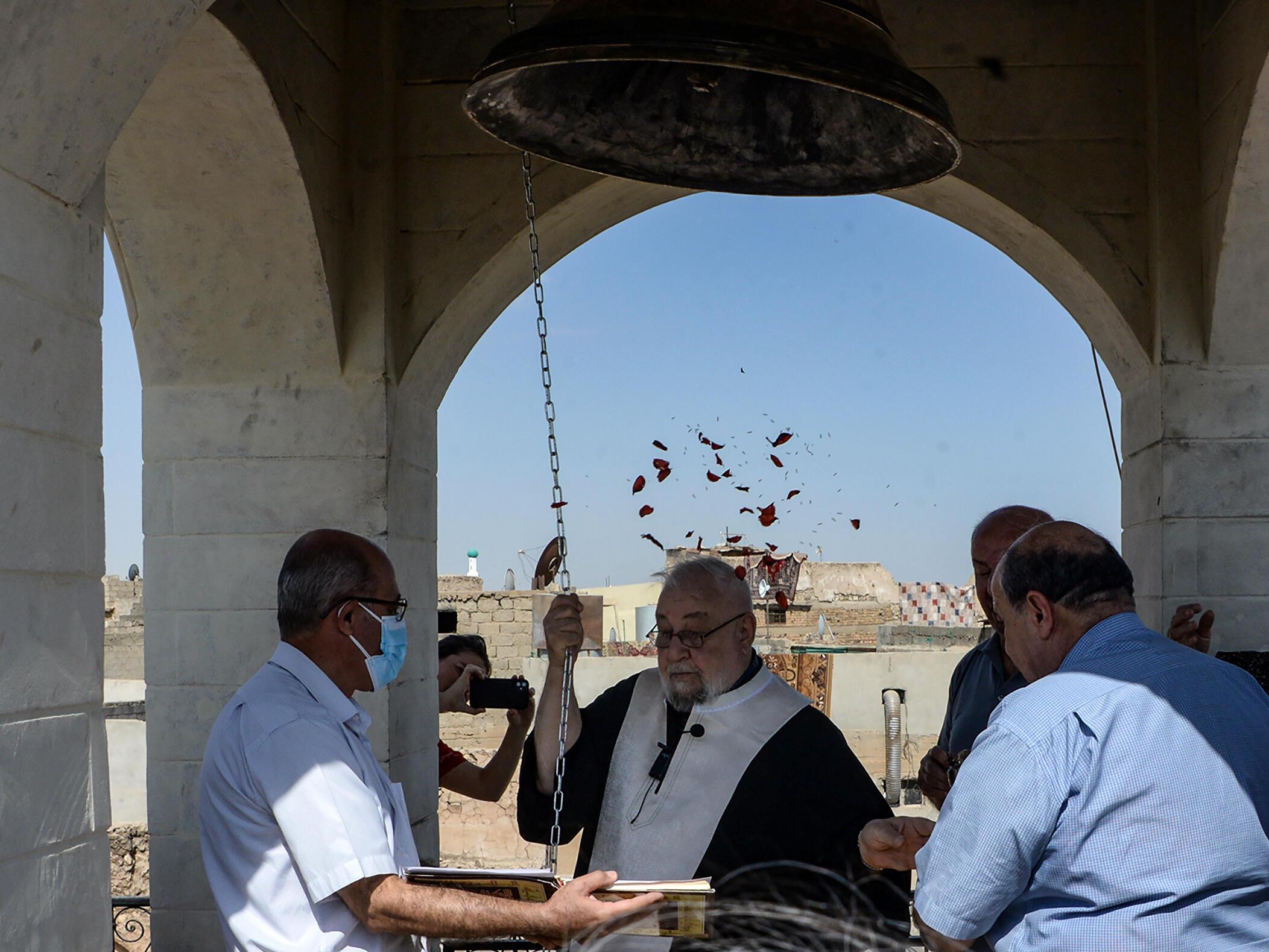 كاهن يقرع جرس كنيسة مار توما السريانية المسيحية في الموصل شمال العراق في 18 أيلول/سبتمبر 2021