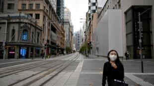 امرأة تسير في شارع شبه مقفر في سيدني بسبب إجراءات الحجر للحد من تفشي فيروس كورونا المستجد، في 30 مارس/آذار 2020