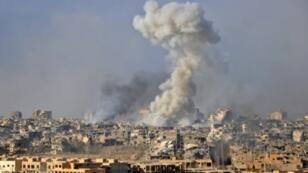 الدخان يتصاعد من المباني بعد ضربة جوية نفذتها القوات الحكومية السورية على مدينة دير الزور بتاريخ 31 تشرين الأول/ أكتوبر 2017