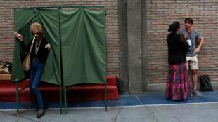 Una mujer pone una pegatina en una urna en una mesa de votación en Santiago antes de las elecciones presidenciales de Chile del 17 de diciembre.