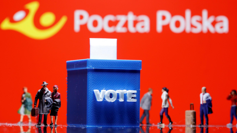 Una urna de votación impresa en 3D y figuras de personas de juguete se ven frente al logo de Poczta Polska (Oficina de Correos de Polonia) en esta ilustración tomada el 4 de mayo de 2020