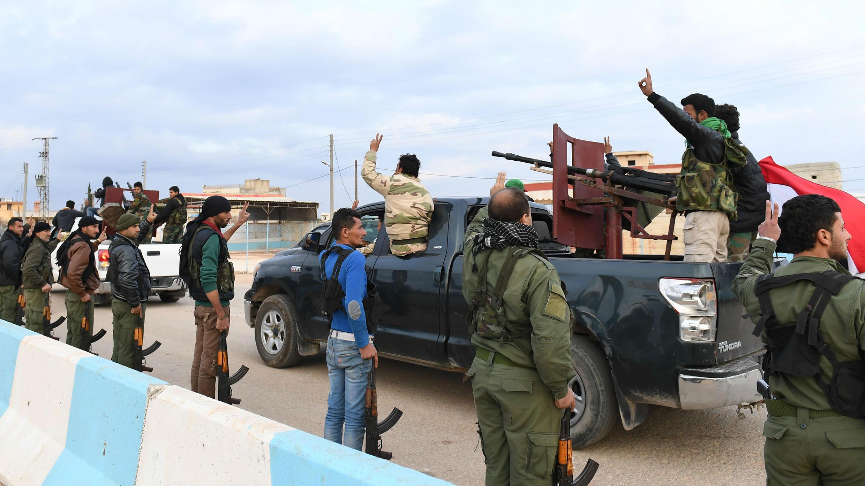 """Una foto tomada el 20 de febrero de 2018 muestra a combatientes kurdos haciendo el gesto de victoria mientras reciben a un convoy de combatientes pro sirios que arriban a la región de Afrin, al norte de Siria. Las fuerzas kurdas dijeron en un comunicado que los combatientes partidarios del régimen desplegados en esa tomarán posiciones y """"participarán en la defensa de la unidad territorial de Siria y sus fronteras"""" para contrarrestar la ofensiva del ejército turco en el área."""