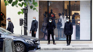Employees stand outside a reopened Chanel fashion boutique in Paris on May 11, 2020.