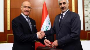 وزير الرياضة العراقي الجديد عدنان درجال (الى اليسار) خلال عملية التسليم والتسلم مع سلفه أحمد رياض.