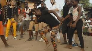 """Image extraite du clip de """"Unforgettable"""" sur laquelle on voit French Montana (en blanc), avec de jeunes danseurs ougandais."""