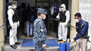 Un guardia de seguridad desinfecta el uniforme y los zapatos de un soldado como medida preventiva contra la propagación del coronavirus, en la entrada de un banco en La Paz, el 20 de abril de 2020