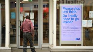 """Un cliente mira una sucursal bancaria casi vacía en el centro de la ciudad inglesa de York el 12 de mayo de 2020, cuyo cartel en inglés dice """"Por favor, deténgase y piense. ¿Necesito realmente entrar?"""""""