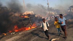 Civiles evacúan la escena de la explosión en el distrito de Hodan, en Mogadiscio, el 14 de octubre de 2017.