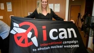 """مديرة """"آيكان"""" تحمل لافتة للمنظمة في جنيف في 6 تشرين الأول/أكتوبر 2017"""