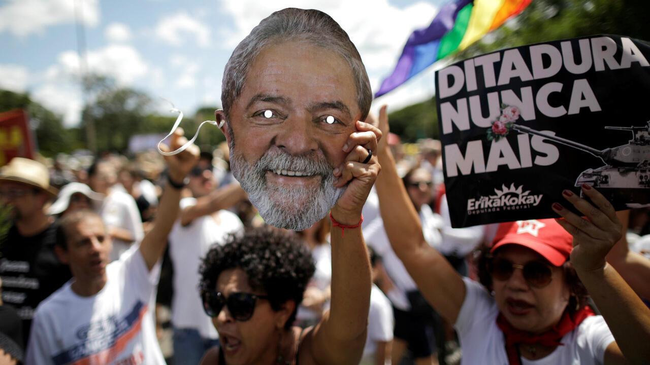 Una manifestante sostiene una máscara del expresidente Luiz Inácio Lula da Silva durante una manifestación en Brasilia en contra de los actos conmemorativos del golpe de Estado de 1964. Marzo 31 de 2019.