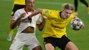 Le buteur de Dortmund Erling Haaland (d) à la lutte avec le défenseur de Séville Jules Koundé en 8e de finale aller de Ligue des champions, le 17 février 2021 à Séville