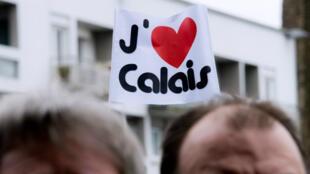 """Des manifestants tiennent des pancartes """"J'aime Calais"""" lors d'un rassemblement en soutien aux commerçants, le 24 janvier 2016."""