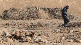 """ضابط عراقي في موقع يشتبه أنه مقبرة جماعية لضحايا تنظيم """"الدولة الإسلامية""""، 18 تشرين الثاني/نوفمبر 2016 قرب الموصل."""