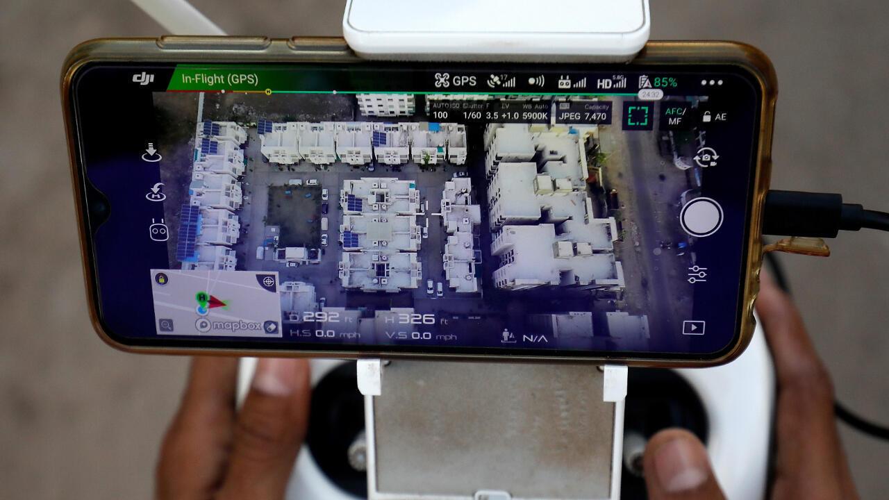 Oficiales de policía usan un dron para monitorear el movimiento de personas en un área residencial durante la cuarentena por coronavirus en Ahmedabad, India, el 29 de marzo de 2020.