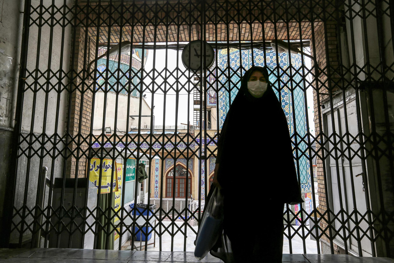 Una mujer pasa por la puerta cerrada frente al Imamzadeh Saleh en el distrito Shemiran de la capital iraní, Teherán, el 25 de abril de 2020.