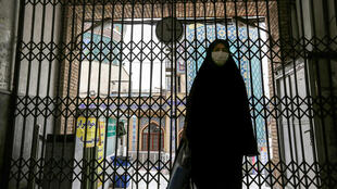 A woman walks past the closed gate outside the Imamzadeh Saleh in the Iranian capital Tehran's Shemiran district on April 25, 2020.