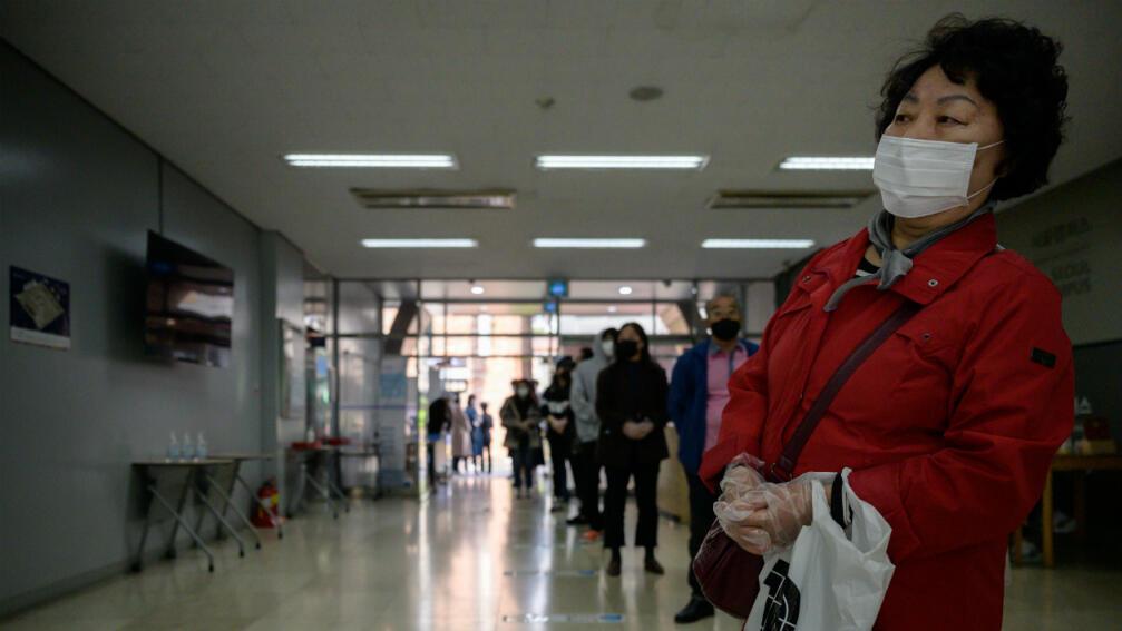 Votantes con mascarillas y guantes hacen fila para emitir sus votos durante las elecciones parlamentarias en Seúl, Corea del Sur, el 15 de abril de 2020.