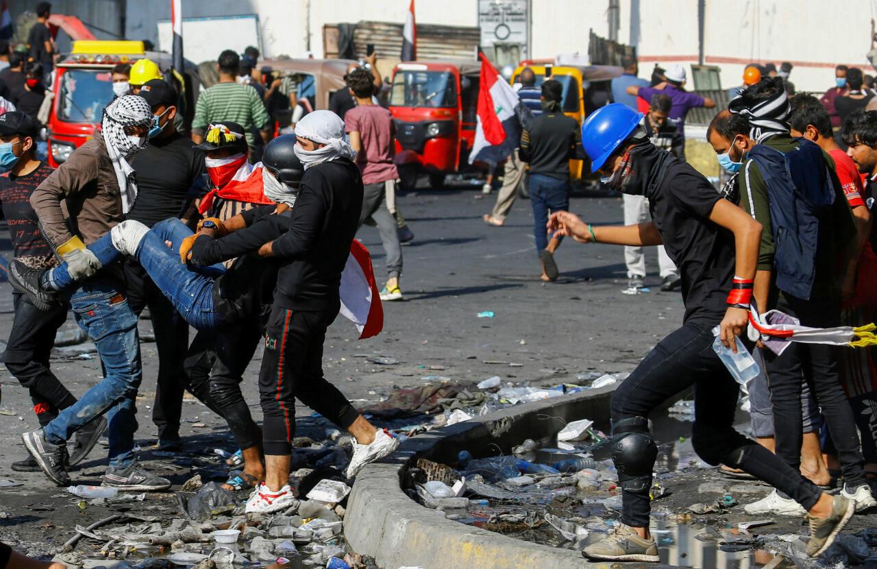 متظاهرون عراقيون يحملون مصابا أثناء الاحتجاجات، 15 نوفمبر/تشرين الثاني 2019.
