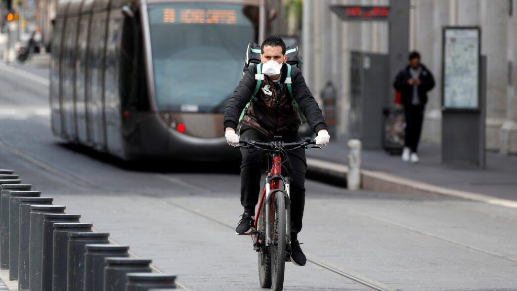Un livreur à vélo porte un masque de protection, à Nice, le 17 mars 2020