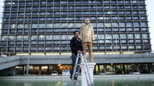 L'artiste Itay Zalait devant sa statue dorée.