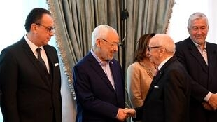 Le président tunisien Béji Caïd Essebsi (à d.) salue le leader du parti islamiste Ennahda Rached Ghannouchi lors d'une réunion avec les partis, syndicats et patrons le 13 janvier 2018 à Tunis.