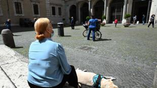 امرأة تتنزه مع كلبها في روما في 3 أيار/مايو 2020
