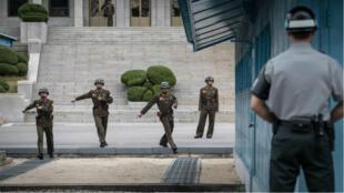 Un soldat sud-coréen (à droite) et des soldats nord-coréens se font face de part et d'autre de la ligne de démarcation.