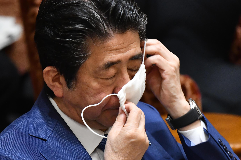 El primer ministro de Japón, Shinzo Abe, se ajusta una mascarilla durante una sesión del Parlamento. Tokio, Japón, el 30 de abril de 2020.