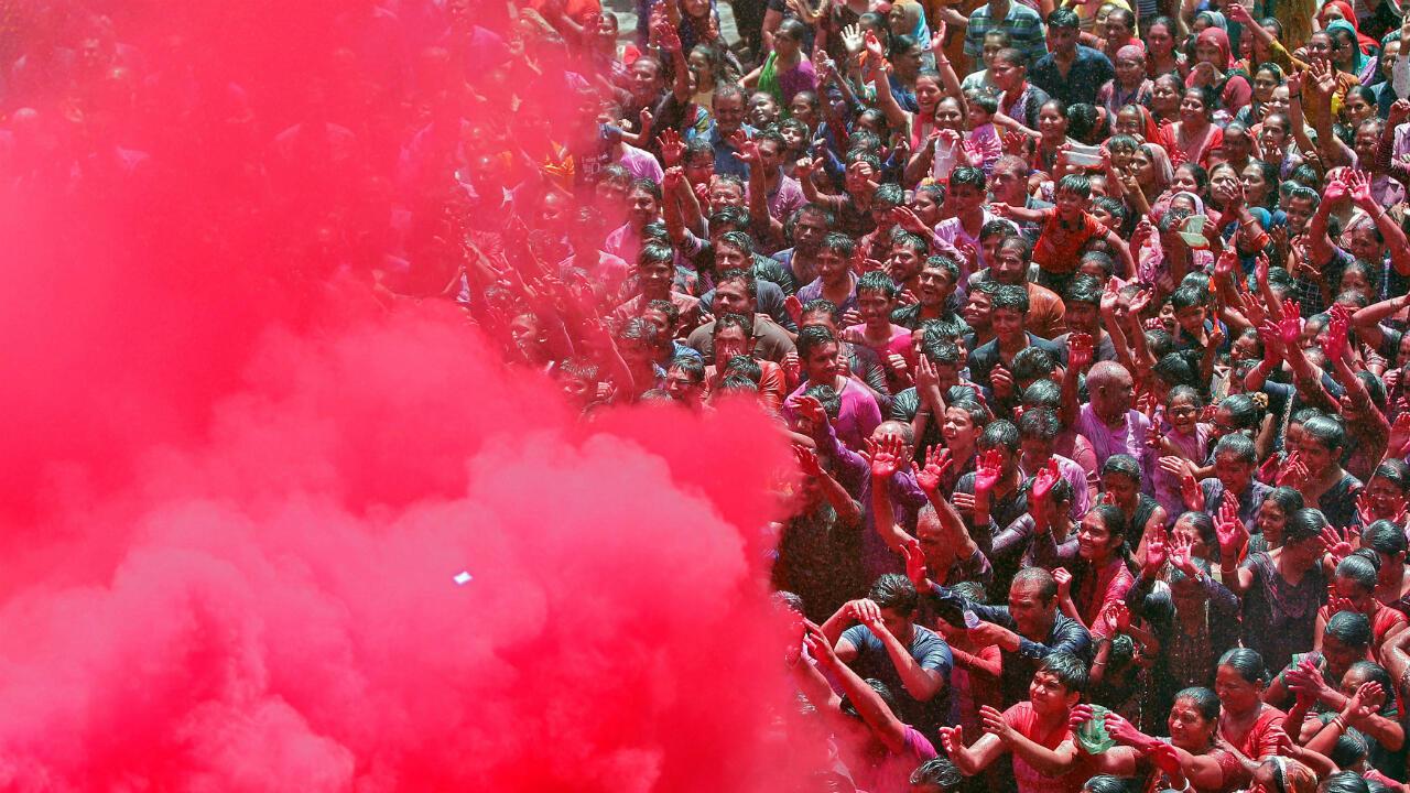 Una multitud de devotos hindúes reza mientras lanzan sobre ellos polvos de colores en el templo en Ahmedabad, India, el 20 de marzo de 2019.