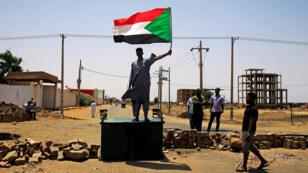 Un manifestante sudanés tiene una bandera nacional mientras se encuentra en una barricada a lo largo de una calle, exigiendo que el Consejo militar de transición del país entregue el poder a los civiles, en Jartum, Sudán, el 5 de junio de 2019.