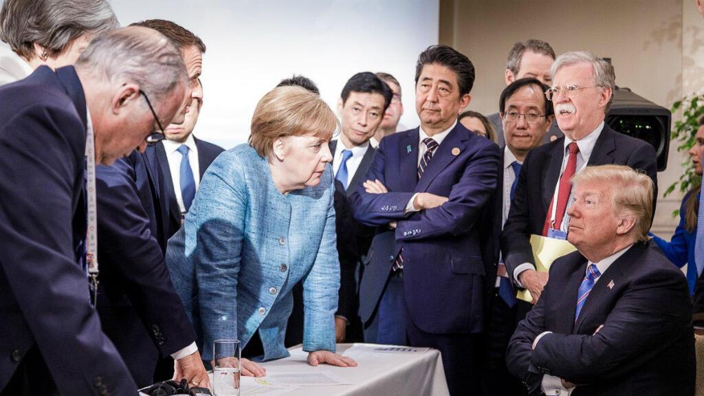 El presidente Donald Trump conversa con la canciller alemana Angela Merkel, rodeado de otros líderes del G7 durante una reunión de la cumbre del G7 en La Malbaie, Quebec, Canadá. 9 de junio 2018.