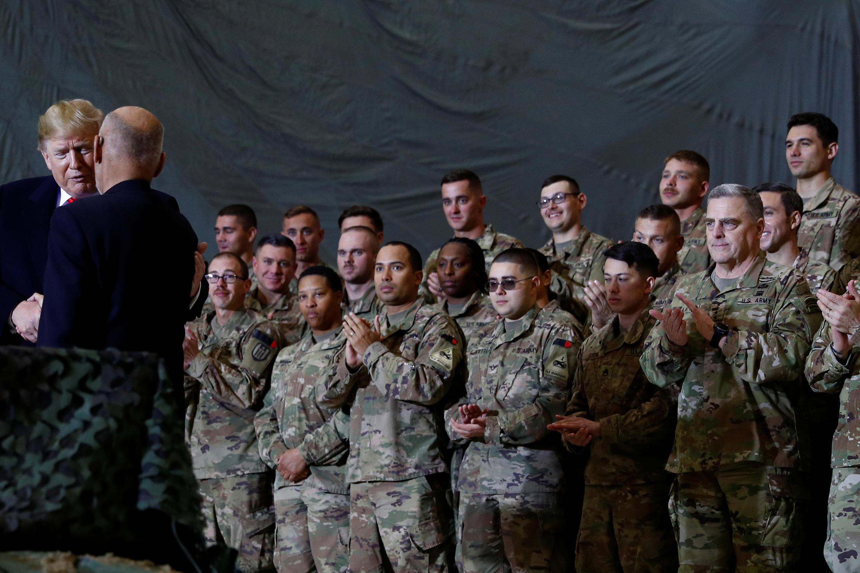 الرئيس الأميركي دوانلد ترامب مصافحاً الرئيس الأفغاني أشرف غني وخلفهم جنود أميركيون في قاعدة باغرام الجوية قرب كابول. 28/11/2019