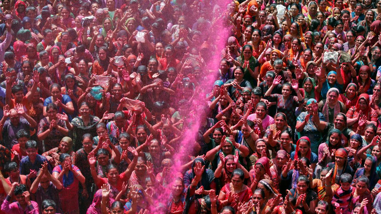 Devotos hindúes rezan mientras lanzan sobre ellos polvos de colores en el templo en Ahmedabad, India, el 20 de marzo de 2019.