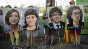 Des manifestants avec des portraits des leaders catalans en prison ou en exil, le 14 juillet à Barcelone.