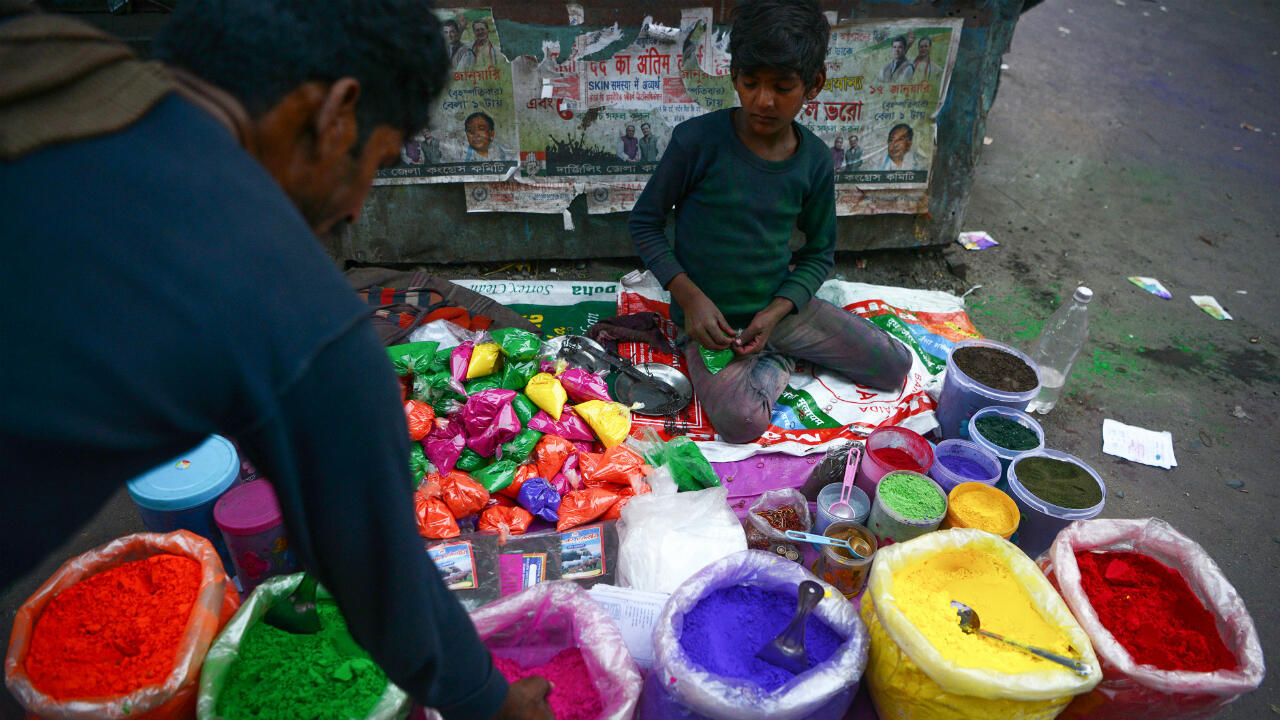 Un niño vende polvos de colores conocidos como 'Gulal', utilizados en el festival Holi. Siliguri, India, el 17 de marzo de 2019.