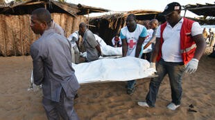 Des secours évacuent le corps d'une victime sur une des plages de Grand-Bassam, dimanche 13 mars 2016.