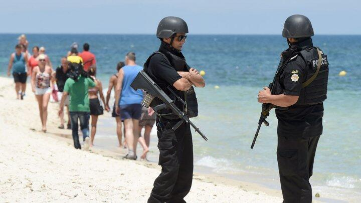 Police stand on July 3 on the Tunisian beach that was the site of a deadly gun attack.