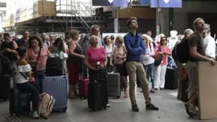 Des voyageurs consultant le panneau d'affichage de la gare Montparnasse, le 28 juillet 2018.