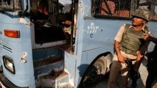 شرطي هندي يتفقد الاضرار داخل حافلة تعرضت لإطلاق نار في كشمير في 25 حزيران/يونيو 2016