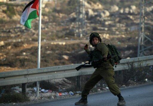 جندي إسرائيلي يرمي قنبلة صوتية باتجاه متظاهرين فلسطينيين قرب مستوطنة بيت إيل 4 أكتوبر 2015