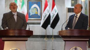 وزير الخارجية الإيراني محمد جواد ظريف إلى جانب نظيره العراقي فؤاد حسين في مؤتمر صحافي عقب لقائهما في بغداد، 19 تموز/يوليو 2020