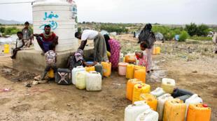 عدد من الأشخاص يملأون أوعيتهم بالماء في مخيم للنازحين في محافظة حجة شمال اليمن في 16 كانون الأول/ديسمبر 2019