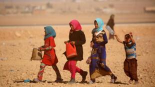 Sirios de la ciudad de Deir Al Zor, al este de la ciudad, quienes fueron desplazados por la guerra contra el grupo Estado Islámico, vistos en las afueras del campamento de Ain Issa, el 23 de septiembre de 2017.