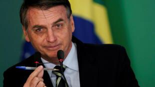 El presidente de Brasil , Jair Bolsonaro, muestra un bolígrafo durante una ceremonia de firma del decreto que facilita las restricciones de armas en Brasil , en el Palacio de Planalto en Brasilia, Brasil , 15 de enero de 2019.