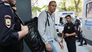 El líder de la oposición rusa Alexéi Navalny es escoltado al vehículo policial después de su juicio en un tribunal de Moscú. 27 de agosto de 2018.