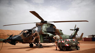 French soldiers work on a Tiger attack helicopter at a base in Gao, northern Mali, on August 1, 2019.