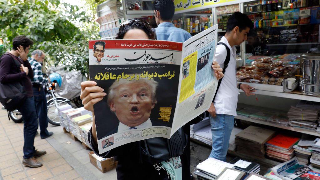 Una mujer iraní lee un periódico con la imagen del presidente de Estados Unidos, Donald Trump, en la portada.