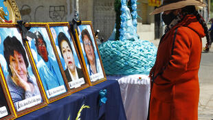 A woman looks at photos of health workers in Puno, Peru who died from Covid-19