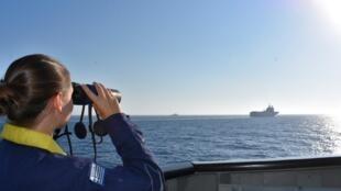 Una mujer mira a través de binoculares, mientras los barcos griegos y franceses navegan durante un ejercicio militar conjunto en el mar Mediterráneo.