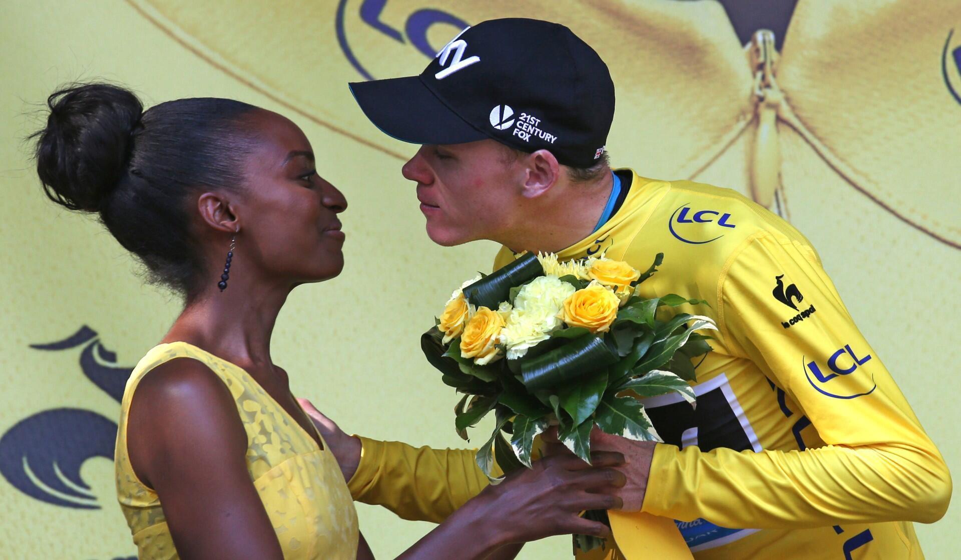 El británico y cuatro veces ganador del Tour de Francia Christopher Froome besa a una anfitriona en el podio durante la edición 2015 de la carrera.